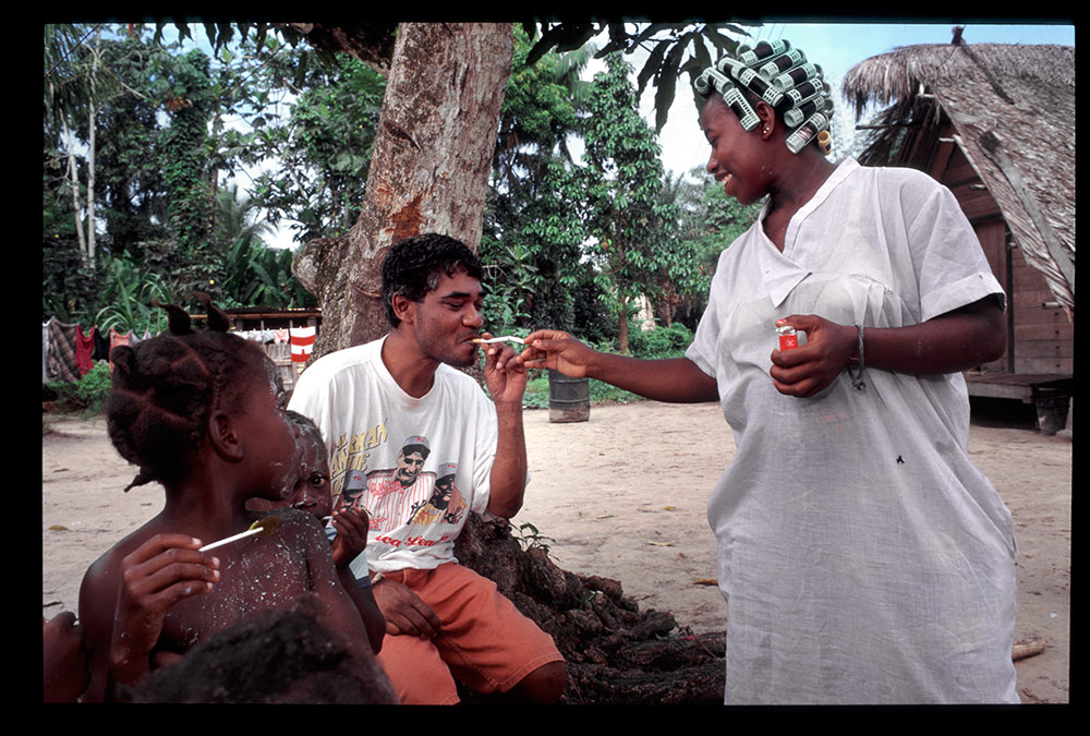 1996 - WINTI SURINAME - KLINIEK SANTIGRON - Guno met dorpsbewoners. Werk, drank en seks tijdens de winti behandeling zijn verboden door de god Gan Pa / Guno with villagers. Work, drink and sex during the winti treatment are forbidden by the god Gan Pa