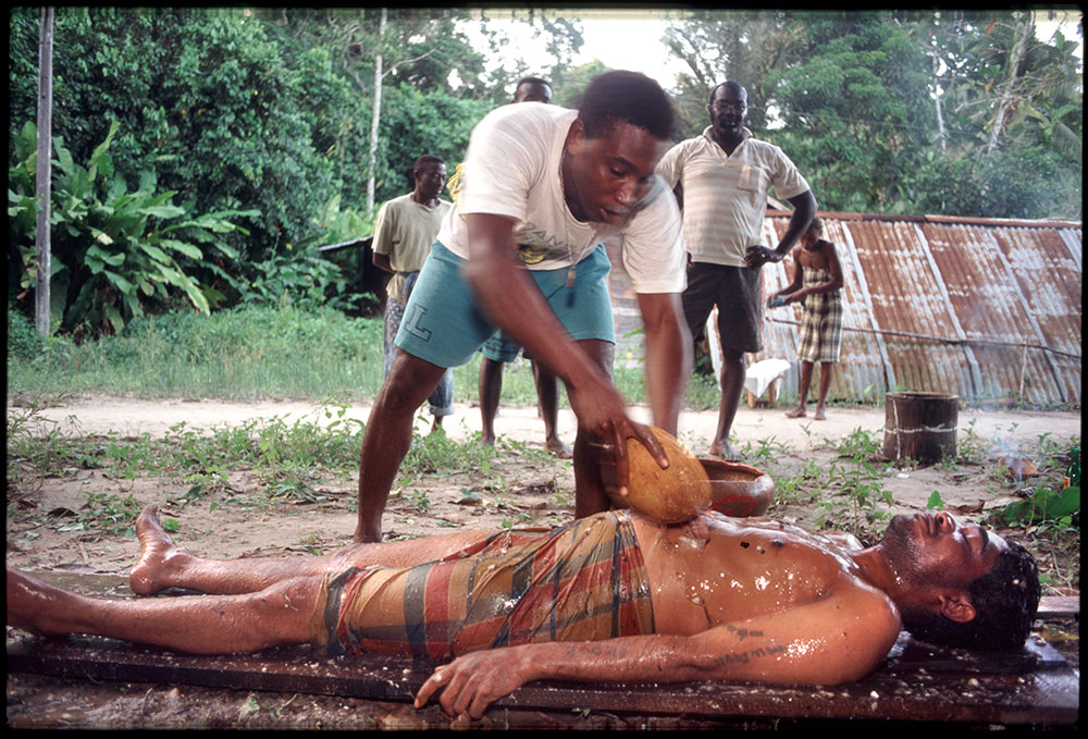 1996 - WINTI SURINAME - KLINIEK SANTIGRON - Guno in trance tijdens de winti ceremonie voor het scheiden van goede en kwade geesten, door bediender van god Gan Pa / Guno in trance during the winti ceremony for the separation of good and evil spirits, by the servant of god Gan Pa