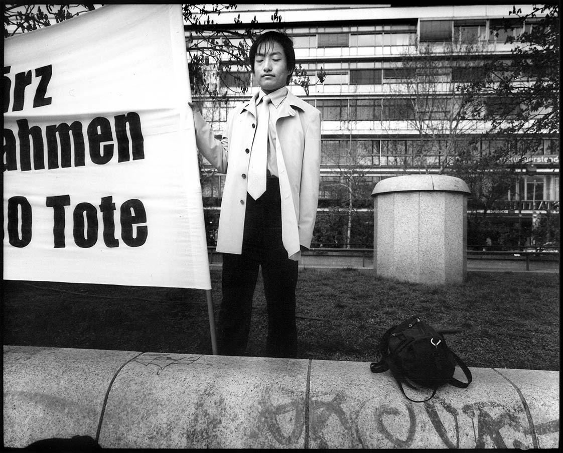 PROTEST - Germany, Berlin – Gedächtniskirche Breitscheidplatz 7 april 2002. Jonge Chinees protesteert met ingehouden adem tegen schending burgerrechten door Chinees regime / ENG: Chinese young man protests against violation of civil rights by Chinese regime. From project FANTASYBERLIN